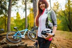 Bild des Mädchens mit dem Sturzhelm, der auf Hintergrund des Fahrrades steht Lizenzfreie Stockfotografie