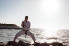 Bild des männlichen Karatekämpfers, der auf Steinseehintergrund aufwirft Lizenzfreie Stockfotos