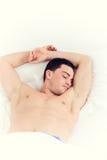 Bild des Mannes mit beiden Händen oben auf Kissen schlafend im Bett Lizenzfreie Stockfotografie