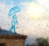 Bild des Mannes mit einem Regenschirm auf einem Fenster in den Tropfen des Regens Stockbild
