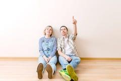 Bild des Mannes und der Frau, die auf Boden sitzen Stockfotografie