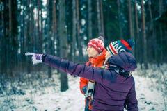 Bild des Mannes und der Frau, die Hand vorwärts im Winterwald zeigen Stockbild