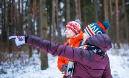 Bild des Mannes und der Frau, die Hand vorwärts im Winterwald zeigen Lizenzfreies Stockfoto