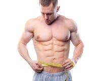 Bild des muskulösen Mannmaßes seine Taille mit messendem Band in den Zentimeter Schuss lokalisiert auf weißem Hintergrund Stockfotografie