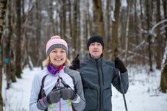 Bild des netten Sports Frau und des Mannskifahrens im Winterwald Stockfotos