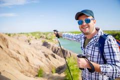 Bild des netten touristischen Mannes mit dem Rucksack, der vorwärts mit Stöcken für das Gehen auf Hügel ausdehnt Stockbild