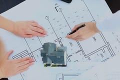 Bild des neuen Musterhauses auf Architekturplanplan am Schreibtisch Stockfotos