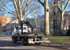 Bild des Parkabschleppwagenfahrzeugs mit Kran auf leerer Stadtstraße neben Park Stockbild
