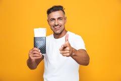 Bild des positiven Mannes 30s in den weißen T-Shirt Holdingpass- und -reisekarten lizenzfreie stockfotografie