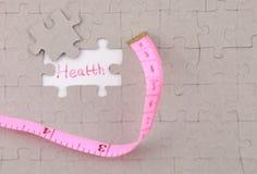 Bild des Puzzlespielstückes mit Gesundheit und rotem Machthaber Stockbild