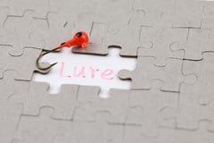 Bild des Puzzlespielstückes mit Köder und Angelhaken Stockfotografie
