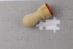 Bild des Puzzlespielstückes mit Lösung und Beamtdichtung Stockbilder