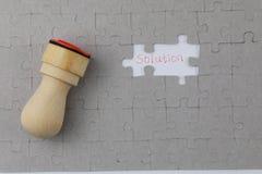 Bild des Puzzlespielstückes mit Lösung und Beamtdichtung Lizenzfreie Stockbilder