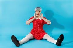 Bild des schönen dollish Mädchens mit dem kurzen hellvioletten Haar, das rotes Kleid über blauem Hintergrund trägt Stockbild