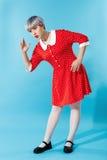 Bild des schönen dollish Mädchens mit dem kurzen hellvioletten Haar, das rotes Kleid über blauem Hintergrund trägt Stockfoto