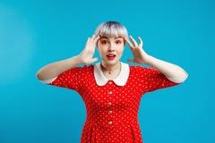 Bild des schönen dollish Mädchens mit dem kurzen hellvioletten Haar, das rotes Kleid über blauem Hintergrund trägt Lizenzfreie Stockfotos