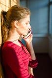 Bild des schönen Mädchens der jungen Frau mit Schatten von den Jalousien auf dem Plaudern des Mobilhandys Stockfotografie