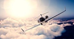 Bild des schwarzen generischen Designprivatjetluxusfliegens im blauen Himmel bei Sonnenuntergang Enormes Weiß bewölkt Hintergrund Stockfotografie