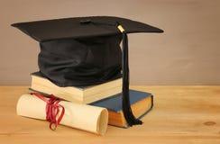 Bild des schwarzen Hutes der Staffelung über alten Büchern nahe bei Staffelung auf hölzernem Schreibtisch Ausbildung und zurück z lizenzfreie stockfotos