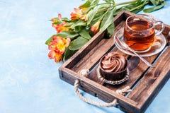 Bild des schwarzen Tees in der Schale, Kuchen Stockbild