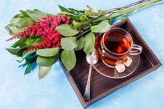 Bild des schwarzen Tees, rote Blumen Stockfoto