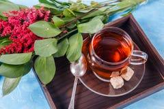 Bild des schwarzen Tees, rote Blumen Lizenzfreies Stockfoto