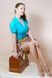 Bild des Sitzens auf dem sexy reizend junge Frau des Nähmaschinekastens sexy Pinupmädchen im Rock und in blauem Hemd, die Spaß ha Stockbild