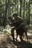 Bild des Soldaten im Sturzhelm mit Maschinenpistole und Hund Stockbild