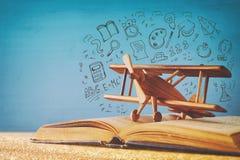 Bild des Spielzeugflugzeuges und -buches über Holztisch mit Satz zurück zu Schule-infographics Lizenzfreies Stockbild