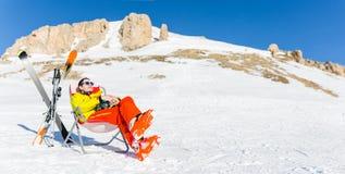 Bild des Sports bemannen das Sitzen auf Stuhl nahe bei Skis und Stöcken auf Hintergrund von schneebedeckten Bergen Lizenzfreie Stockbilder