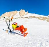 Bild des Sports bemannen das Sitzen auf Stuhl nahe bei Skis und Stöcken auf Hintergrund von schneebedeckten Bergen Stockbilder