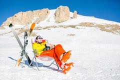 Bild des Sports bemannen das Sitzen auf Stuhl nahe bei Skis und Stöcken auf Hintergrund von schneebedeckten Bergen Stockbild