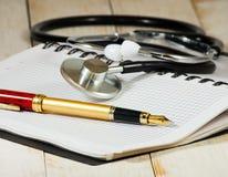 Bild des Stethoskops, der Notizbücher und des Stiftes auf einem weißen Hintergrund Stockbilder