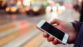 Bild des Telefons mit schwarzem Schirm in Mann ` s Hand auf unscharfem Hintergrund Lizenzfreie Stockfotos