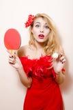 Bild des Tischtennis-Schlägerballs u. der blonden hübschen Frau des eleganten schönen Zaubermädchens dazedly im roten Kleid mit Bl Stockfotos