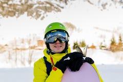 Bild des tragenden Sturzhelms des sportiven Mannes mit Snowboard gegen Hintergrund von schneebedeckten Bergen Lizenzfreies Stockfoto