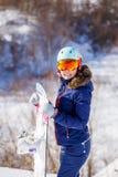 Bild des tragenden Sturzhelms des weiblichen Athleten mit dem Snowboard, der im Park steht Stockfotografie
