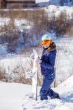 Bild des tragenden Sturzhelms des weiblichen Athleten mit dem Snowboard, der im Park steht Stockfoto