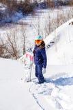 Bild des tragenden Sturzhelms des weiblichen Athleten mit dem Snowboard, der im Park steht Stockbild