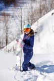 Bild des tragenden Sturzhelms des weiblichen Athleten mit dem Snowboard, der im Park steht Lizenzfreie Stockfotos