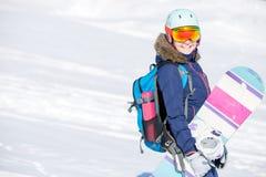 Bild des tragenden Sturzhelms des weiblichen Athleten mit Rucksack und Snowboard Lizenzfreie Stockbilder