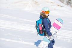 Bild des tragenden Sturzhelms des weiblichen Athleten mit Rucksack und Snowboard Lizenzfreie Stockfotos