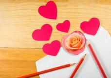Bild des Umschlags, der rosafarbenen Blume, der Bleistifte und der stilisierten Herzen Stockfoto