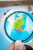 Bild des Vergrößerungsglasgrases auf Weltkarte Stockbild