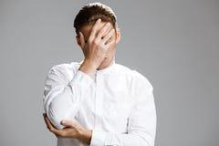 Bild des verwirrten kaukasischen Mannes, der ihn Gesicht versteckt lizenzfreies stockbild