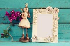 Bild des weißen Rahmens des Weinlesefreien raumes und der netten feenhaften Prinzessin auf Holztisch Lizenzfreie Stockfotos