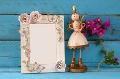 Bild des weißen Rahmens des Weinlesefreien raumes und der netten feenhaften Prinzessin auf Holztisch Stockfotos