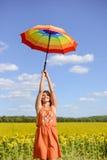 Bild des weiblichen haltenen Regenbogenregenschirmes auf Lizenzfreie Stockfotos
