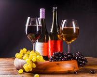 Bild des Weinglases mit Wein, Trauben schwärzen, grünen auf hölzernem Behälter auf Tabelle Lizenzfreie Stockfotografie