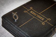 Bild einer Buch Bibelnahaufnahme im schwarzen Ledereinband mit einem Reißverschluss mit einem christlichen hängenden Symbolfisch  Stockbilder